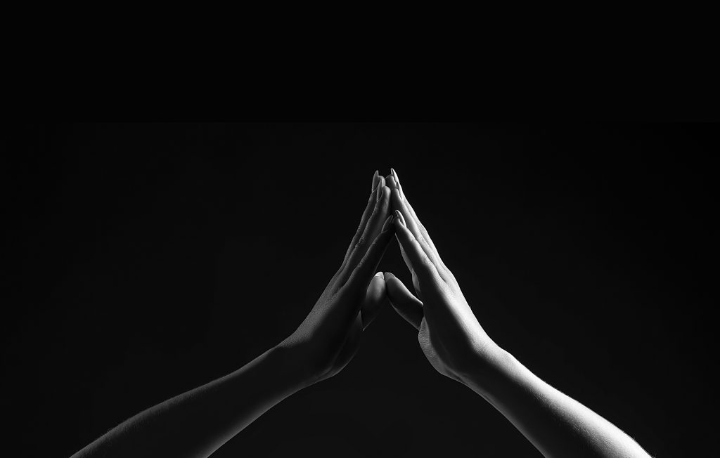Black and white photo of two hands touching. To represent Holistic Therapy.