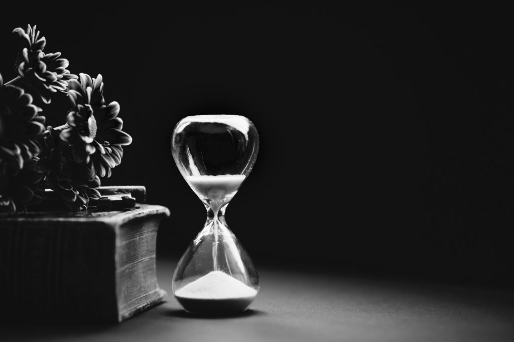 Black and white photo of an hourglass with sand running through it to represent Holistic Therapy.