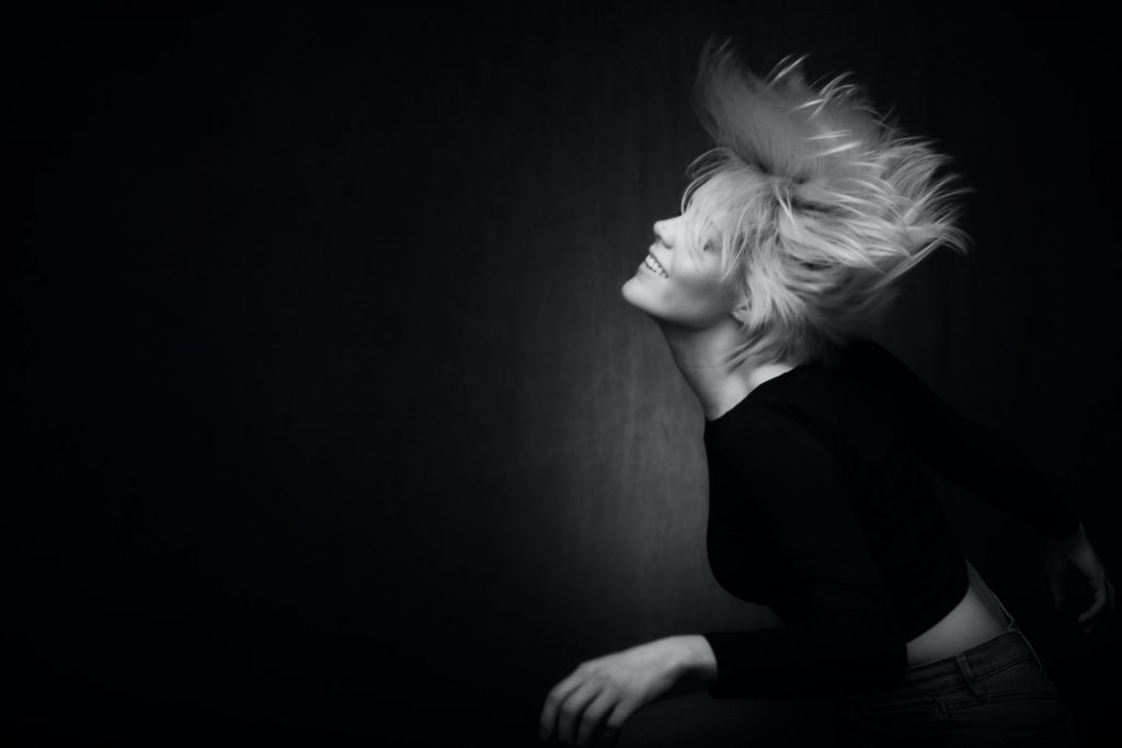 Black and white photo of blonde woman smiling and dancing to represent Holistic Counseling.