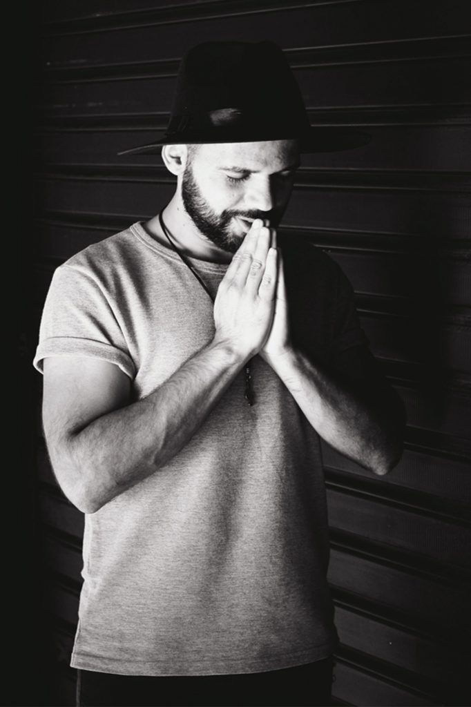 Black and white photo of man with his hands in prayer and eyes closed to represent Men's Sexual Wellness.