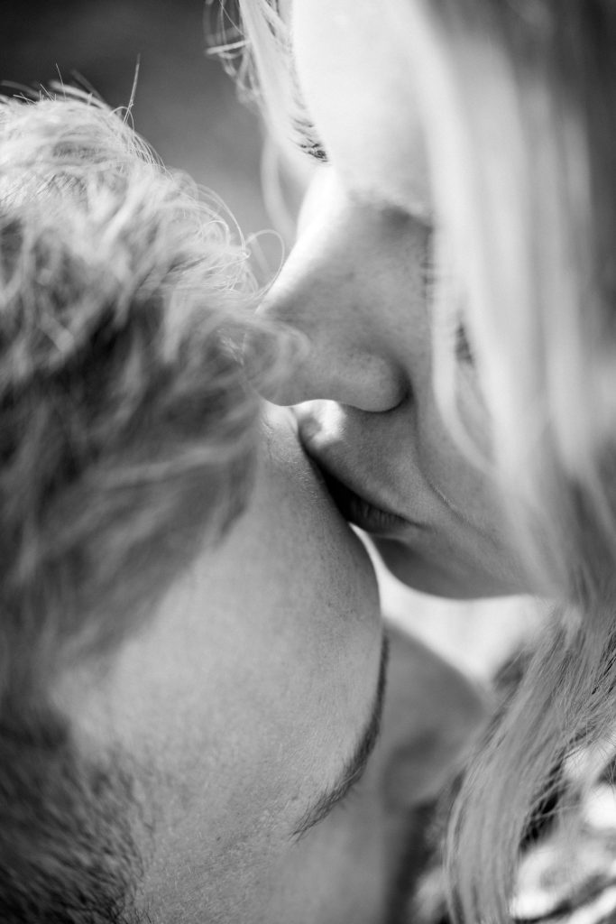 Black and white photo of couple where woman is kissing man on his forehead, to represent Holistic Marriage Counseling.