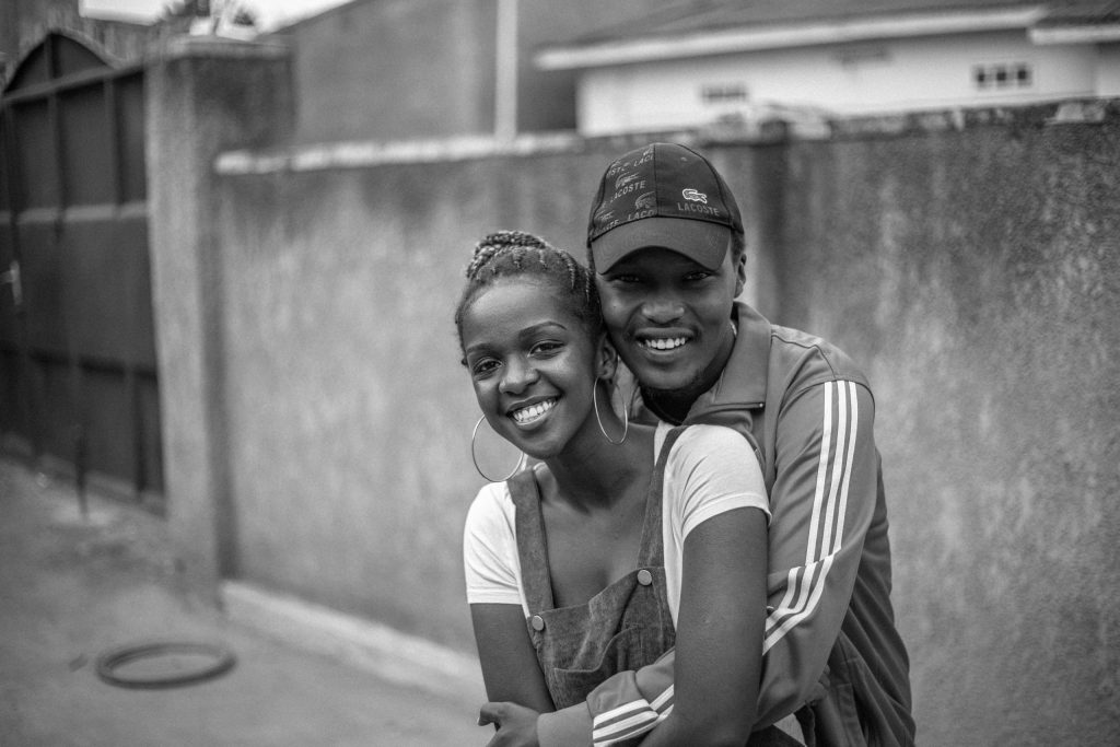 Black and white photo of couple hugging and smiling outside to represent Holistic Couples Counseling.