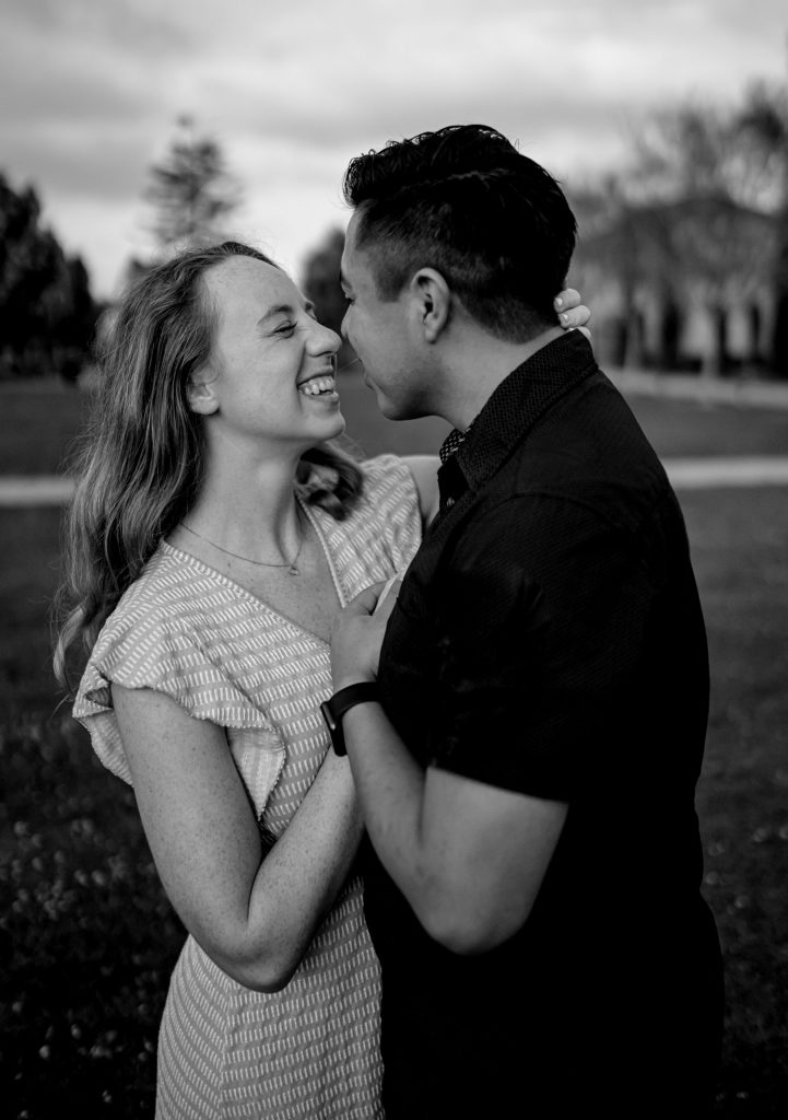 Black and white photo of couple standing outside and smiling at each other to represent Holistic Couples Counseling.